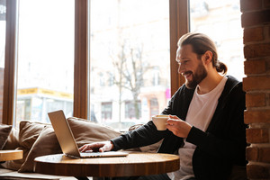Happy Bearded man sitting by the table with cup of coffee and using laptop in cafe