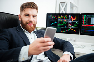 Happy bearded young businessman sitting and using mobile phone in office