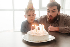 Happy bearded young father sitting near birtday cake with his little son.