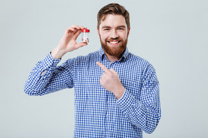 Happy bearded young man holding and pointing on bottle of pills over white background