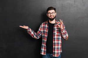 Happy bearded young man in glasses holding copyspace on palm and showing ok gesture over grey background