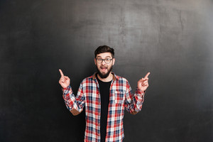 Happy bearded young man in glasses pointing away with both hands over grey background
