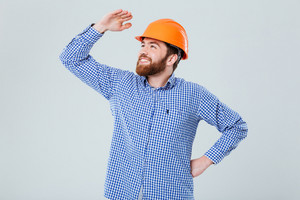 Happy bearded young man in helmet standing and looking far away over white background