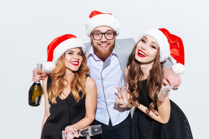 Happy bearded young man with two women in santa claus hats with bottle of champagne over white background