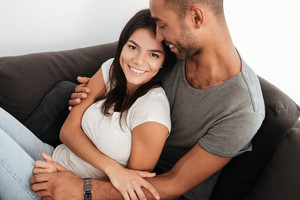 Happy beautiful couple laughing on a sofa at home while hugging. Woman looking at camera.