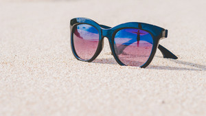 Happy Beautiful Girl Reflecting in Sunglasses on Sand Beach, Bali