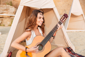 Happy beautiful hippie girl playing guitar while sitting at the tent at beach