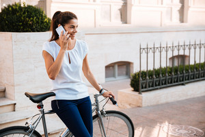 Happy beautiful woman talking on the phone leaning on bicycle on the street
