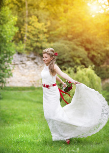 Happy beautiful young bride outside in a summer part at the sunset