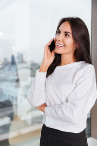 Happy beautiful young businesswoman standing and talking on cell phone near the window