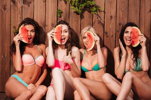 Happy beautiful young girls in bikini eating watermelon at the pool
