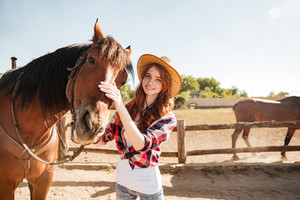 Happy beautiful young woman cowgirl in hat taking care of her horse on ranch