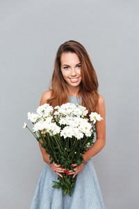 Happy beautiful young woman holding bouquet of flowers over grey background