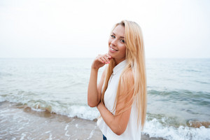 Happy beautiful young woman standing on the beach