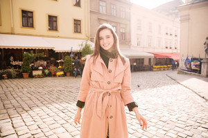 Happy beautiful young woman standing on the street
