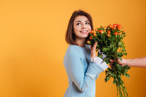 Happy beautiful young woman taking bouquet of flowers over yellow background