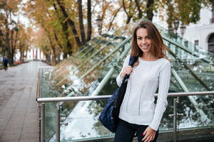 Happy beautiful young woman with backpack walking in the city