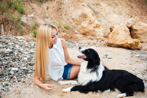 Happy beautiful young woman with cute dog on the beach