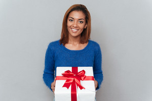 Happy beauty african woman in sweater holding white gift with red tape. Isolated gray background