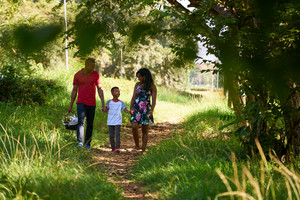 Happy black couple with son walking in city park. African american family with young man, woman and child doing picnic, having fun outdoor.