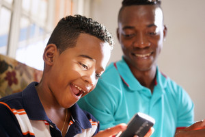 Happy black family at home. African american father and child playing game with cell phone. Hispanic dad and son having fun with smartphone.