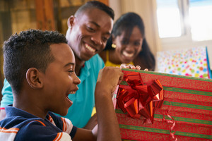 Happy black family at home. African american father, mother and child celebrating birthday, having fun at party. Young boy opening gifts and smiling.