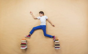 Happy boy is playing with group of books in studio