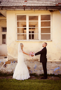 Happy bride and groom posing by the old house