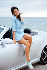 Happy brunette woman and her new car on the beach