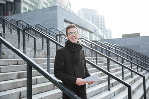 Happy Business man in glasses and warm clothes holding documents in hands and standing on the stairs as well as looking at camera