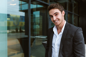 Happy business man in suit standing near the office and looking at camera