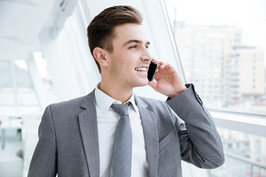 Happy Business man talking at phone near the window and looking away