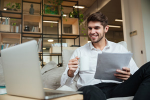 Happy businessman dressed in white shirt sitting in cafe and reading documents while drinking tea. Looking at laptop.