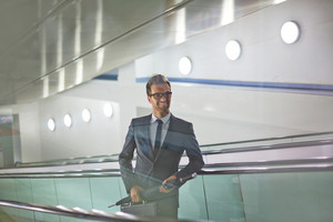 Happy businessman with briefcase and umbrella ascending on escalator of trade center