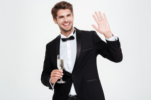 Happy businessman with champagne. waving