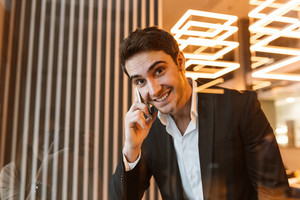 Happy businness man in suit talking on phone behind the glass and looking at camera in office