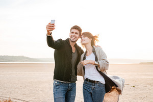 Happy casual couple making selfie photo while standing together on the beach at sunlight