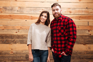Happy casual couple standing together and looking at camera isolated on a wooden background
