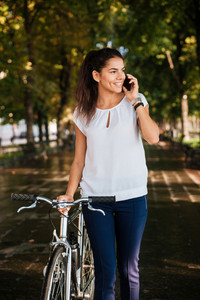 Happy casual girl talking on the phone and walking with bicycle at the city park