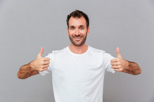 Happy casual man showing thumbs up over grey background