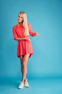 Happy casual woman in red dress standing and pointing finger away isolated on a blue background