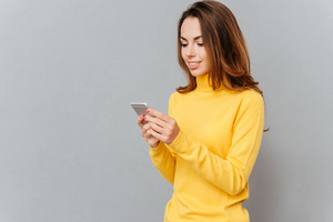 Happy casual woman in yellow sweater using smartphone over gray background