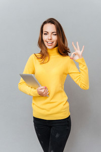 Happy casual woman with tablet computer winking and showing ok sign with fingers isolated on a gray background