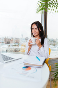 Happy charming young businesswoman drinking coffee and using laptop in office