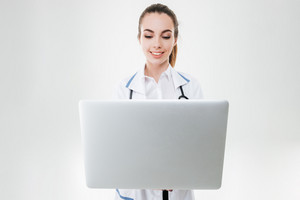 Happy charming young woman doctor using laptop computer over white background