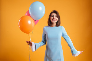 Happy charming young woman in blue dress with colourful balloons over yellow background
