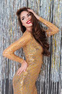 Happy charming young woman in golden dress standing and posing over shining background