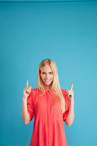 Happy charming young woman pointing two fingers up isolated on a blue background