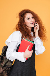 Happy charming young woman with books and backpack talking on mobile phone