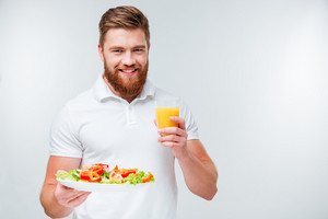 Happy cheerful bearded man holding plate with vegetables and glass of orange juiceisolated on white background